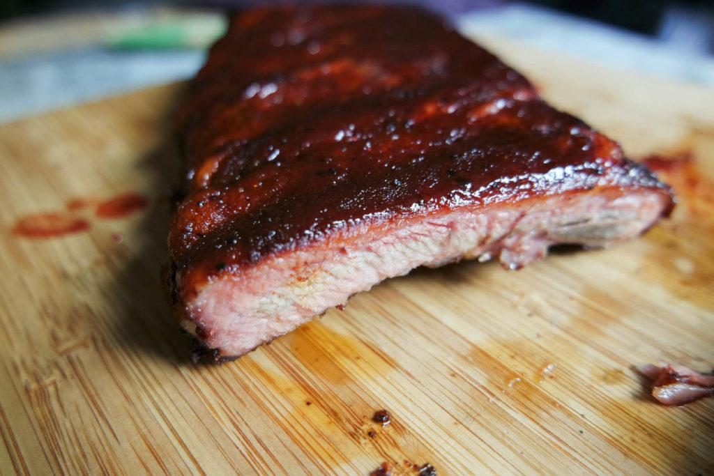 cutting through bbq pork ribs with glaze